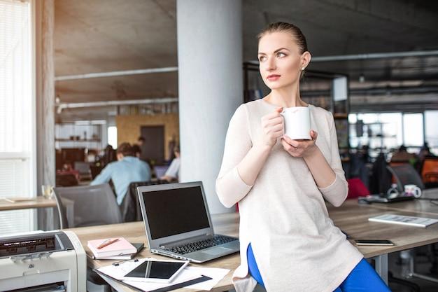 La donna calma e pacifica è seduta sul bordo del tavolo e tiene in mano una tazza di tè