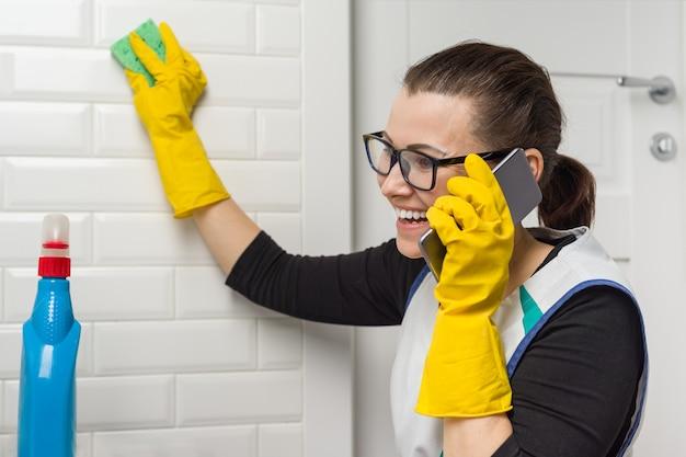La donna casalinga sta pulendo nel bagno e sta parlando al telefono