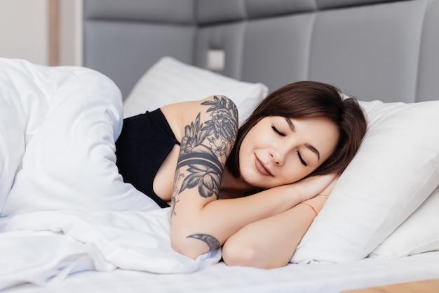 La donna castana addormentata si trova sul letto di mattina sveglia allungando le sue braccia e corpo