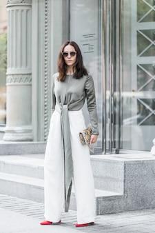 La donna castana che indossa i pantaloni bianchi, gli occhiali da sole e la borsa del leopardo sta camminando sulla strada.
