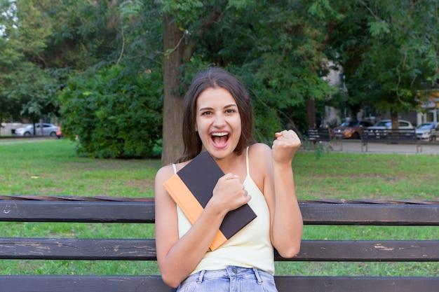 La donna castana sorridente e di risata sta abbracciando il libro e sta mostrando sì nel parco.
