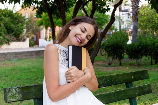 La donna castana sorridente sta abbracciando il suo libro favorito sul banco nel parco