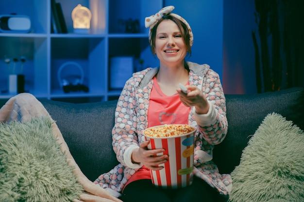 La donna casuale allegra con il fronte divertente che mangia il popcorn e che guarda il film si siede sul sofà