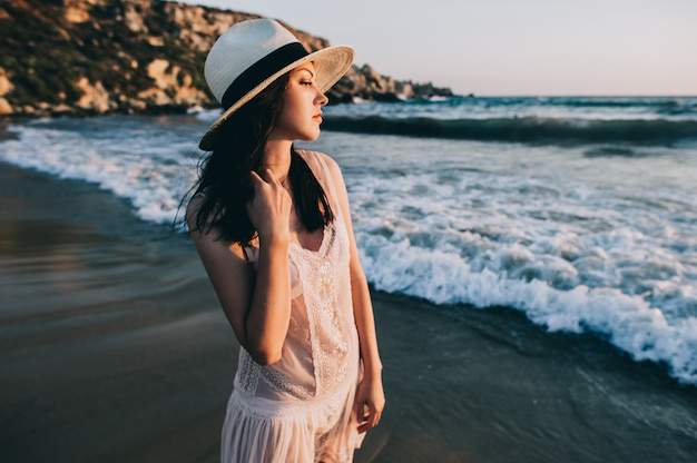 La donna caucasica cammina lungo la bella spiaggia