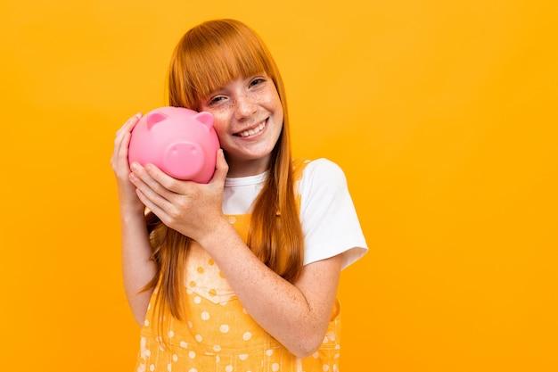 La donna caucasica con capelli rossi giudica il salvadanaio rosa del maiale isolato su fondo giallo