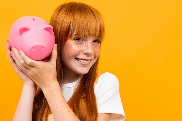 La donna caucasica con capelli rossi giudica il salvadanaio rosa del maiale isolato su giallo