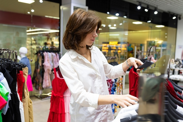 La donna caucasica con l'acconciatura scura e la camicia bianca fa la spesa