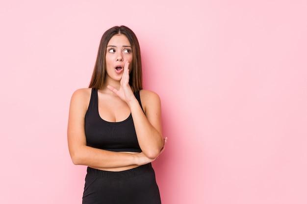 La donna caucasica di giovane forma fisica isolata sta dicendo le notizie di una frenata calde segrete e sta guardando da parte