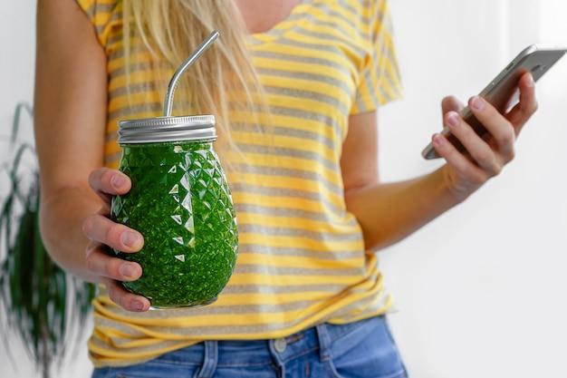 La donna caucasica tiene un barattolo di frullato vegano verde con paglia di metallo