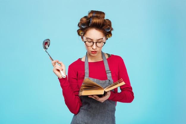La donna cerca la nuova ricetta che tiene il mestolo di minestra in mani