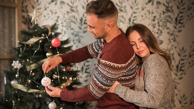 La donna che abbraccia l'uomo dalla parte posteriore in maglioni si avvicina all'albero di natale