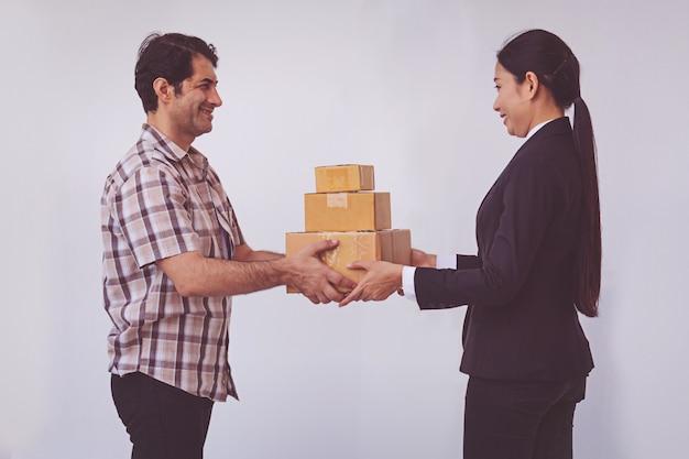 La donna che accetta riceve una consegna di scatole dall'uomo asiatico di consegna