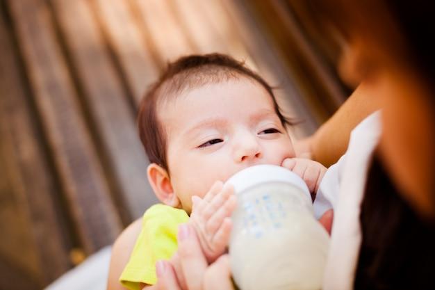 La donna che allatta il suo bambino da una bottiglietta per bambini