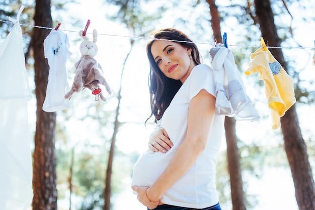 La donna che appende il bambino copre di corda di tela all'aperto