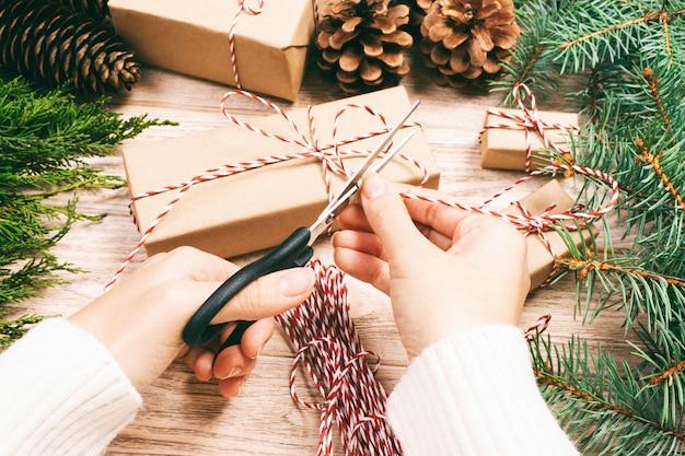 La donna che avvolge il regalo di natale, ragazza prepara i regali di natale con l'albero di abete e la pigna. regalo fatto a mano su legno con decorazioni natalizie. vista dall'alto, copyspace. tonica