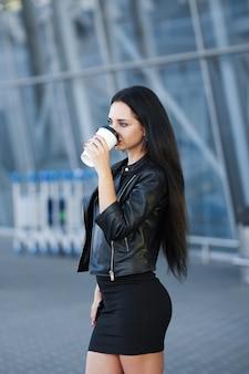 La donna che cammina sulla strada con porta via il caffè