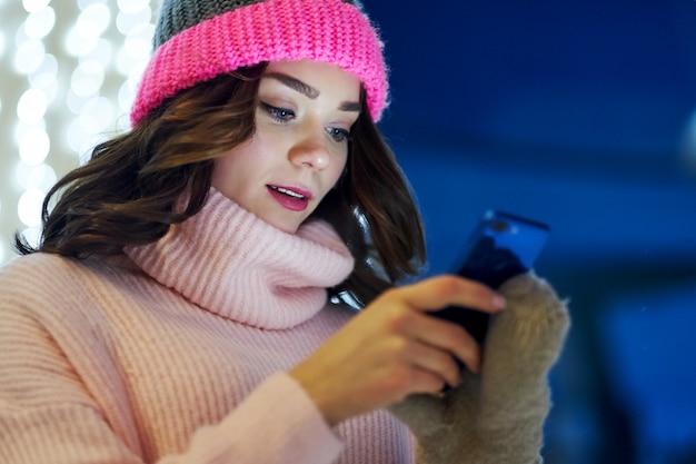 La donna che chiama si congratula con natale o capodanno. femmina con smartphone alla fiera festiva