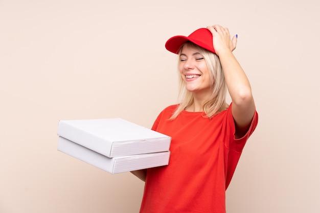 La donna che consegna una pizza in possesso di una pizza sopra un muro isolato ha realizzato qualcosa e intendendo la soluzione