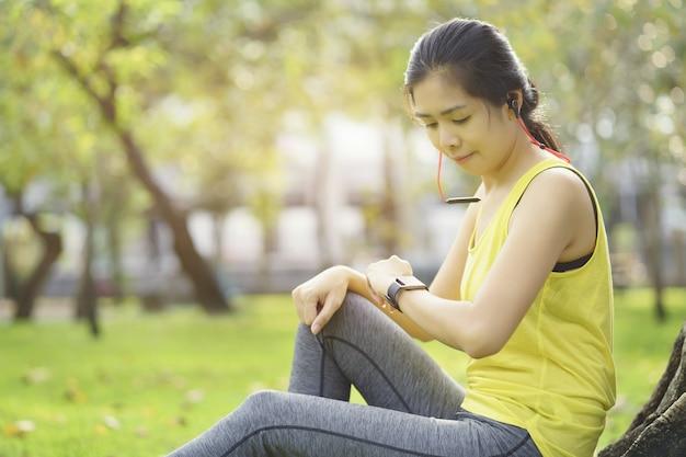 La donna che controlla il progresso sull'orologio intelligente connette ascolta la musica al trasduttore auricolare, dispositivo di fitness indossabile.