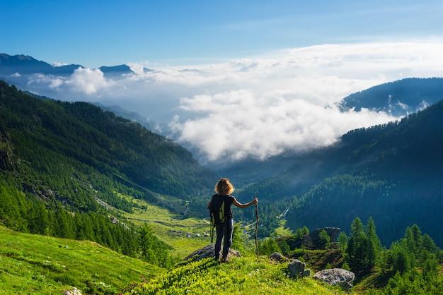 La donna che esamina il paesaggio drammatico si rannuvola la valle, chiaro cielo blu