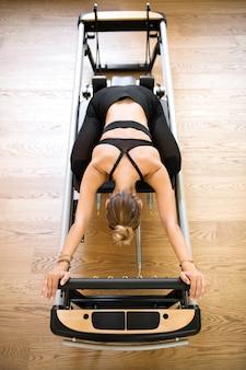 La donna che fa i pilates allunga sul letto del riformatore