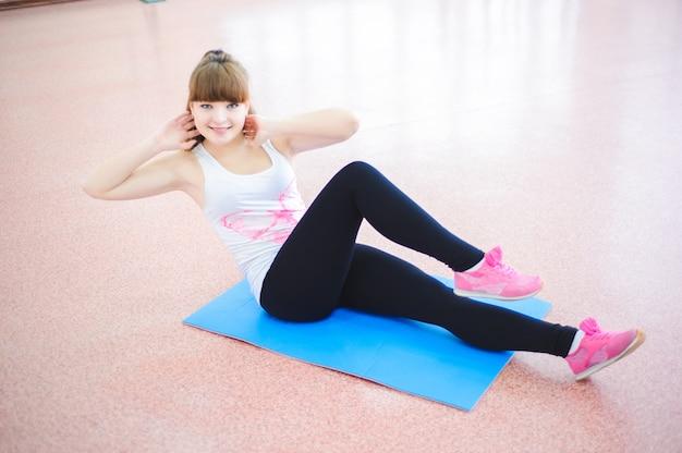 La donna che fa l'allungamento si esercita sul pavimento alla palestra