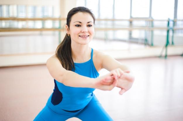 La donna che fa l'allungamento si esercita sul pavimento in palestra