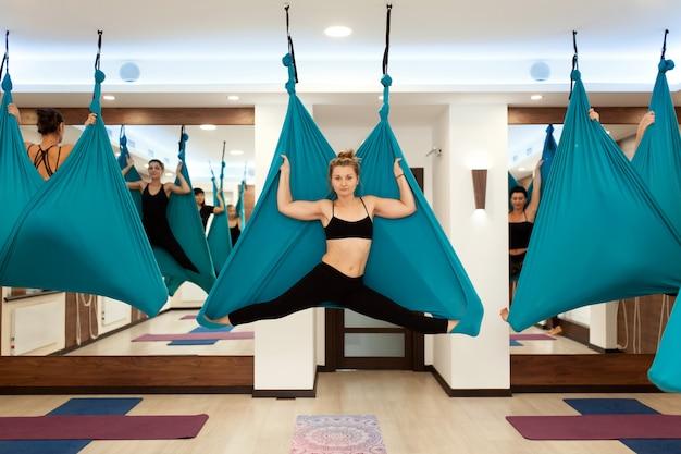 La donna che fa l'yoga della mosca che allunga si esercita in amaca. stile di vita in forma e benessere