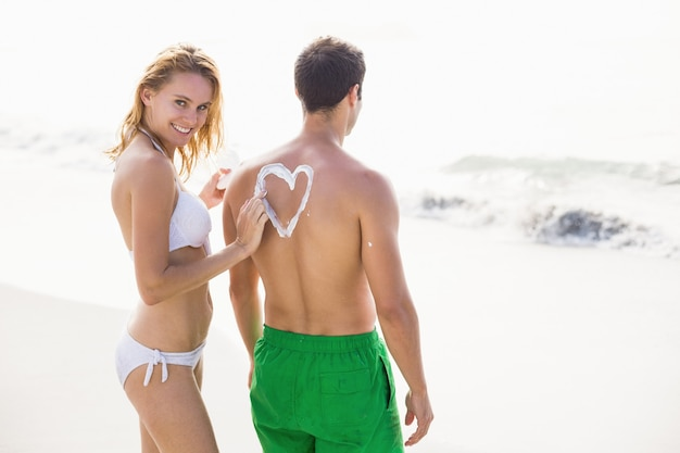 La donna che fa un simbolo del cuore sopra equipaggia la schiena mentre applica una crema solare