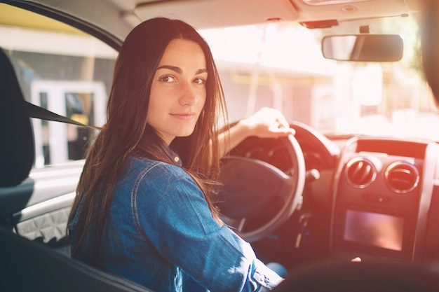La donna che guida la macchina sorridendo