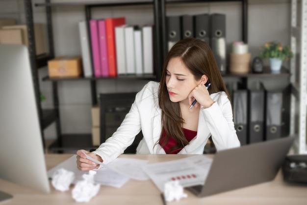 La donna che lavora in tuta bianca sta pensando a un nuovo progetto.