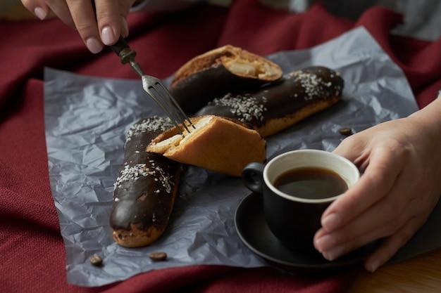 La donna che mangia i eclairs ha riempito di crema, i eclairs francesi tradizionali di cioccolato e la tazza di caffè espresso.