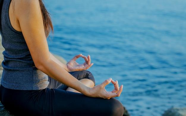 La donna che medita in una posa di yoga sulla spiaggia tropicale.