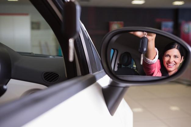 La donna che mostra l'automobile digita lo specchietto retrovisore
