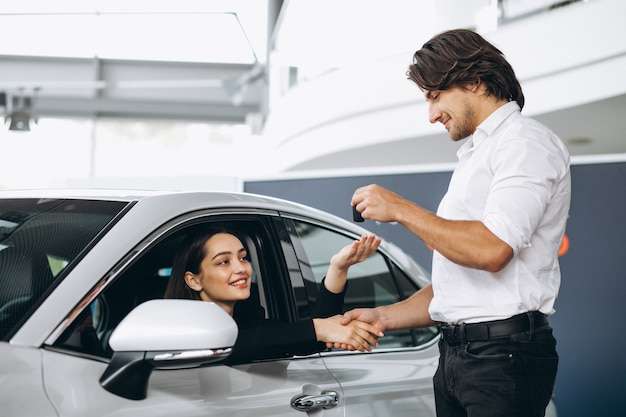 La donna che parla con il maschio seleziona la persona in una sala d'esposizione dell'automobile