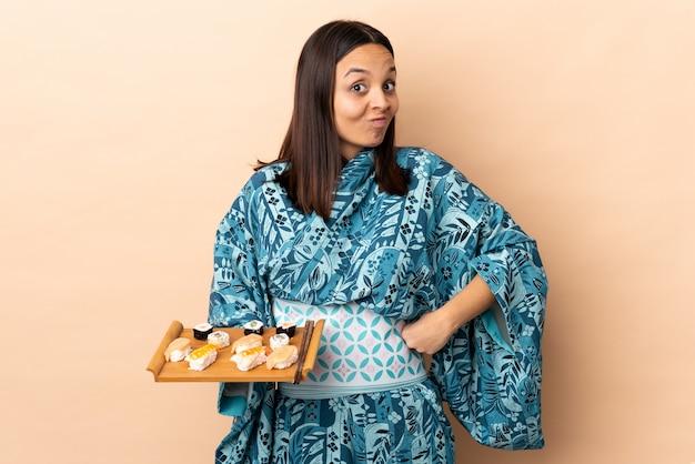 La donna che porta il kimono e che tiene i sushi sopra isolato facendo dubbi gesturing mentre solleva le spalle