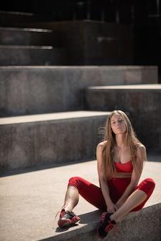 La donna che posa vicino alla fontana della città in palestra copre dopo un allenamento