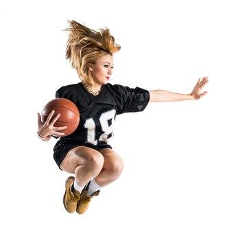 La donna che salta e gioca a basket