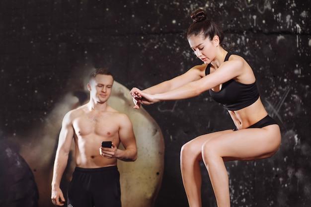 La donna che salta sulla scatola adatta con l'istruttore maschio