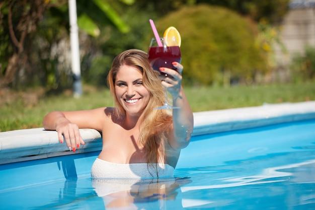 La donna che si rilassa e beve un cocktail alla piscina