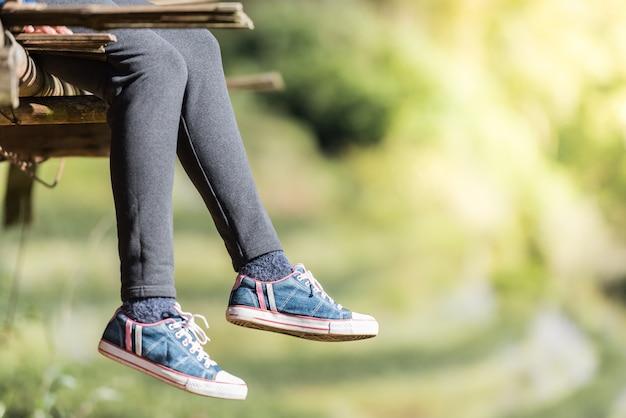 La donna che si siede e si rilassa sul pavimento di legno con le gambe che appendono giù.