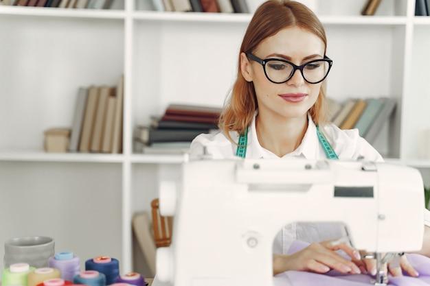 La donna che si siede in studio e cuce il panno