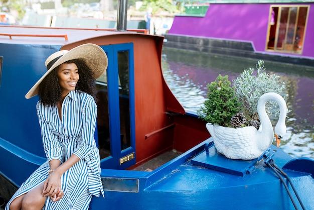 La donna che si siede in una casa galleggiante ha attraccato in un fiume