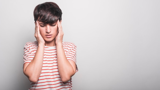 La donna che soffre dal dolore capo ha isolato la priorità bassa bianca