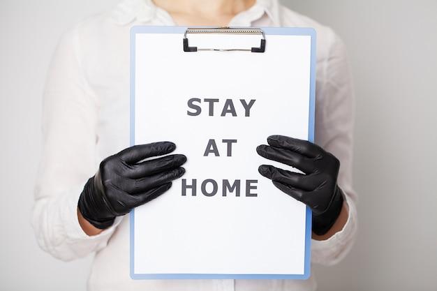 La donna che tiene in bianco con l'iscrizione resta a casa chiedendo di smettere di spargere covid-19