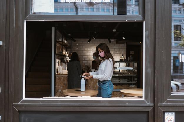 La donna che usando il gel disinfettante pulisce le mani del virus coronavirus al caffè.