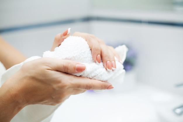 La donna che usando l'asciugamano per asciugarsi le mani si asciuga dopo il lavaggio