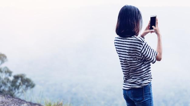 La donna che usando prende un telefono della foto