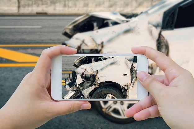 La donna che utilizza lo smartphone scatta foto di un incidente stradale sulla strada