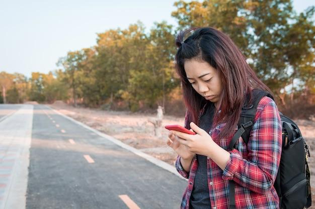La donna che utilizza lo smartphone trova le indicazioni sul lato della strada